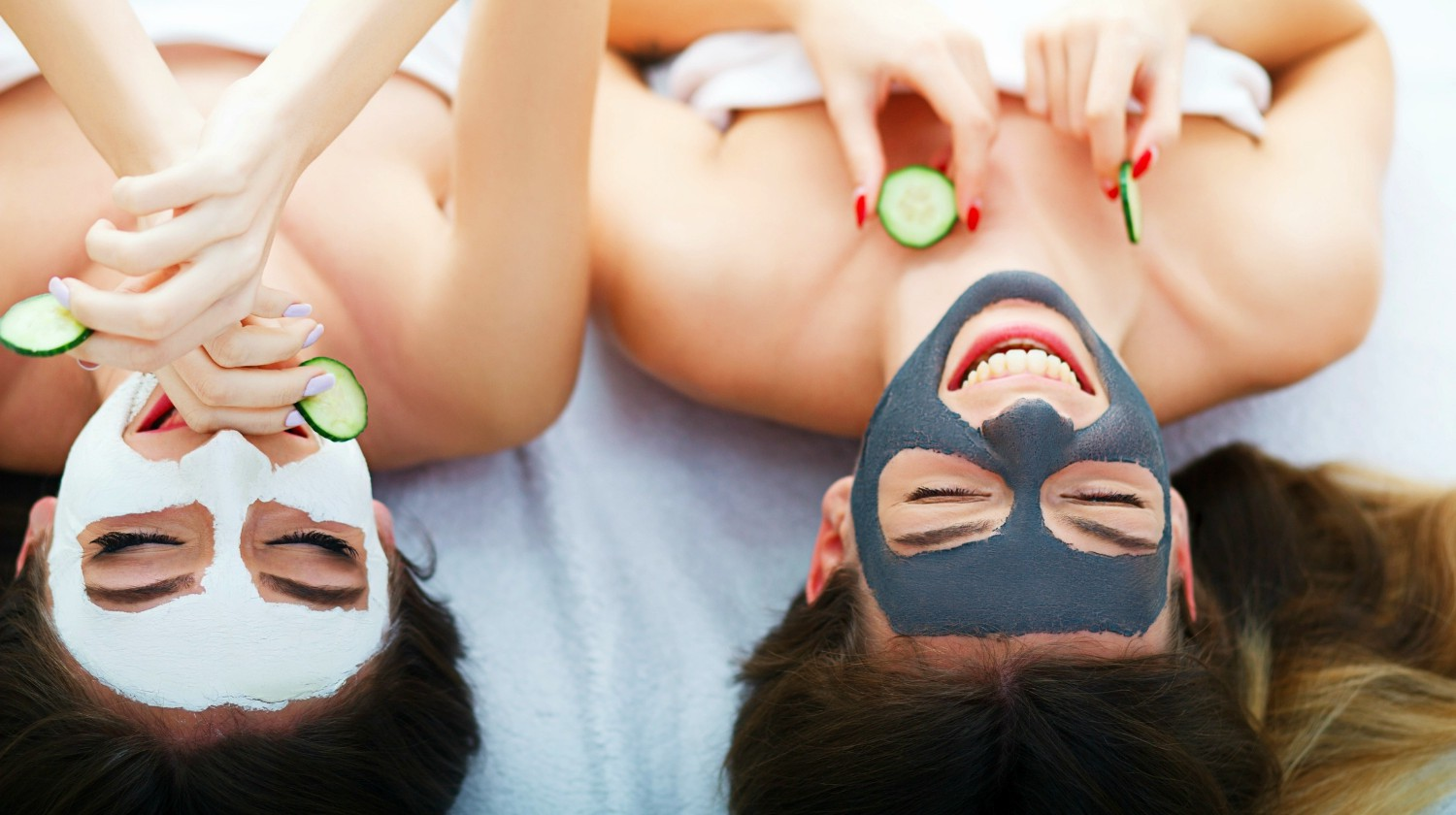 Featured | Two women holding pieces of cucumber on their faces lying the bed | Recipe For A Perfect Girls Night In