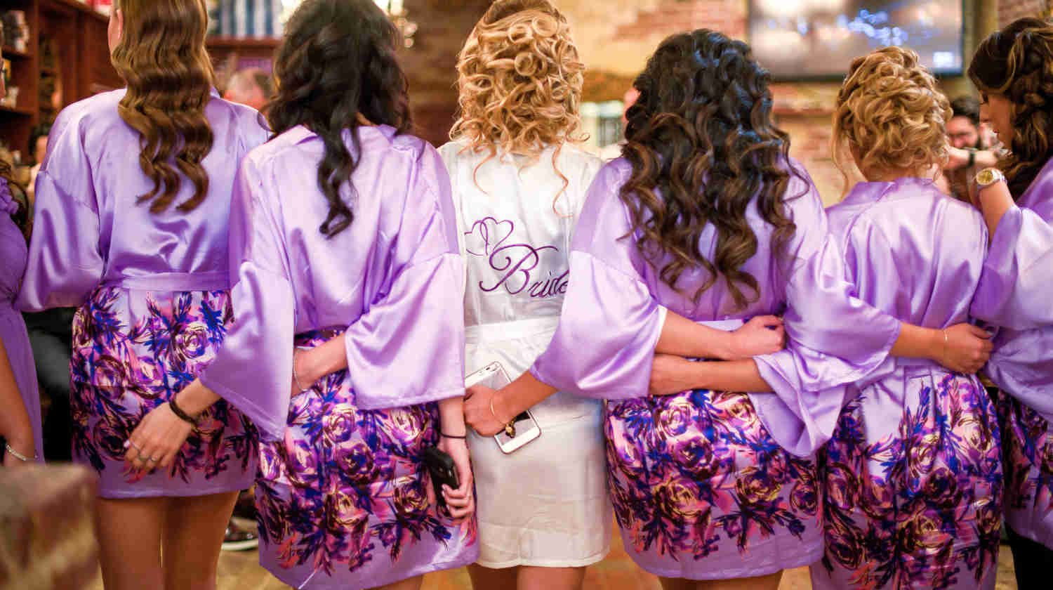 bride and her bridemaids wearing violet robes | Tips On Choosing The Best Bride And Bridesmaid Robes | bridesmaid robes | robes for bridesmaids | featured