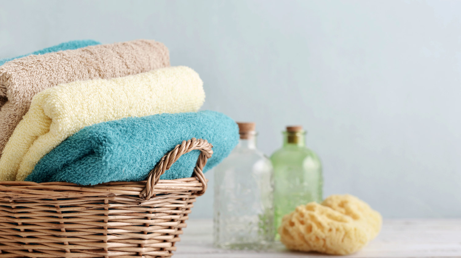 Feature | Bath towels of different colors in wicker basket on light background | How To Get Sour Smell Out Of Towels