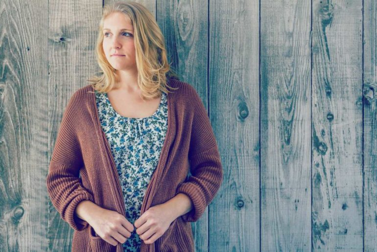 woman wearing brown cardigan leaning on wooden wall | Comfy Lounge Clothes To Wear At Home That's Not Your High School Sweatpants | comfy clothes | comfortable clothes for women | Featured