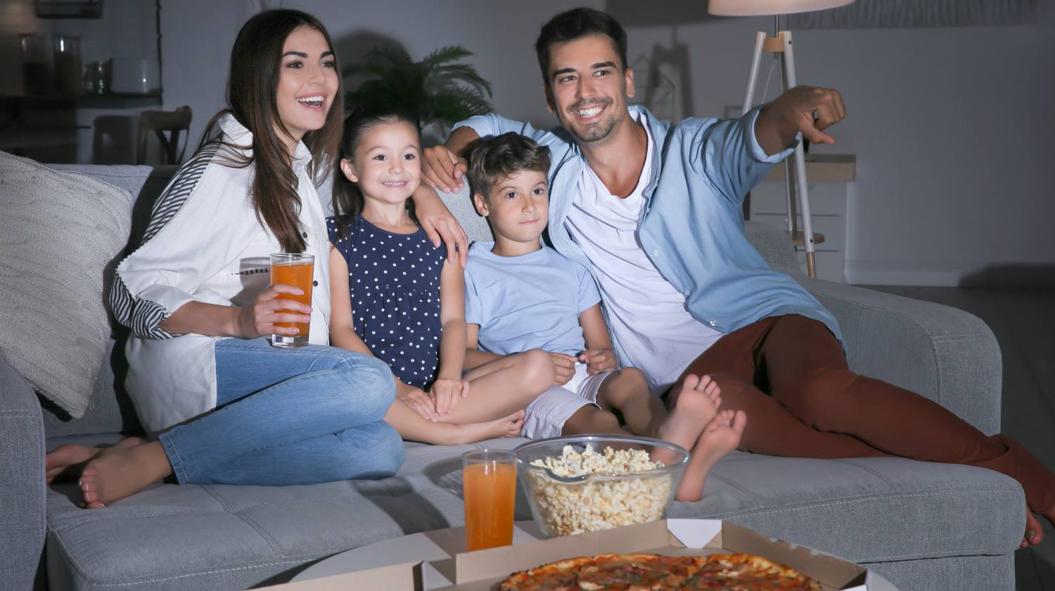 Happy family watching TV on sofa at night | Ways to Make Family Movie Night Even More Fun | movie night | movie night ideas | Featured