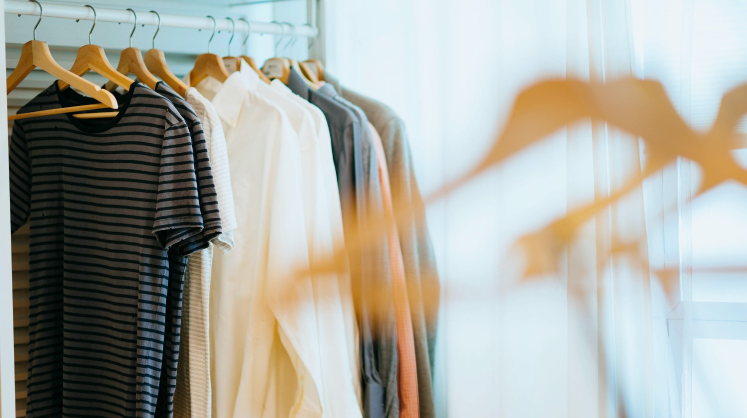 selective focus photography of shirts hanging on rack | How To Start A Minimalist Wardrobe | minimalist wardrobe | minimalist wardrobe men | Featured