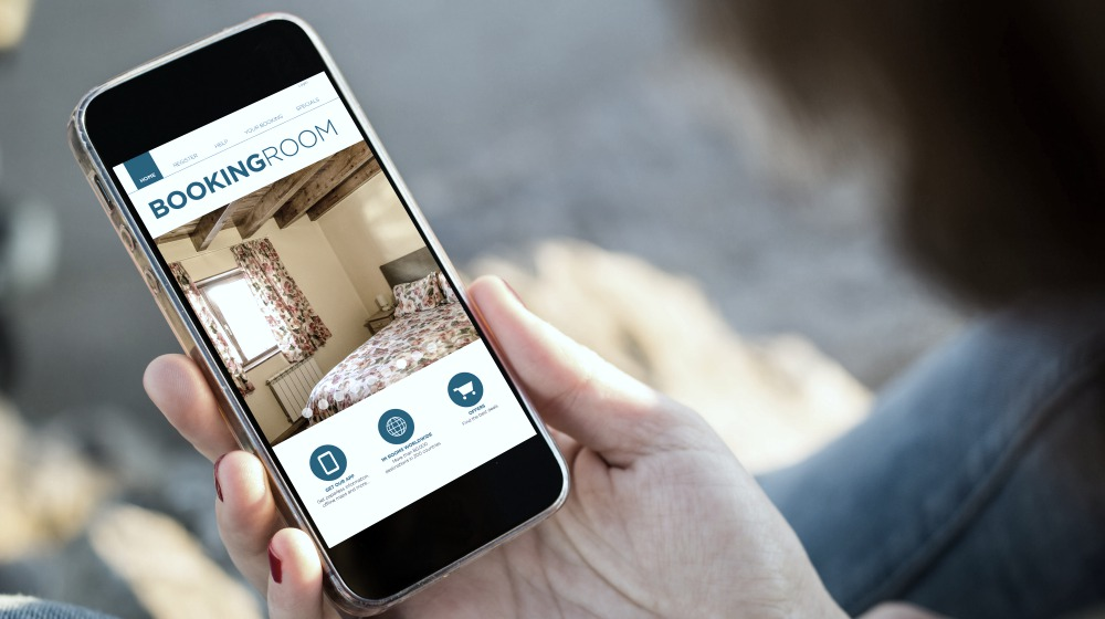 person holding a phone booking a hotel | Ways To Improve Hotel Guest Experience | hotel guest | customer experience