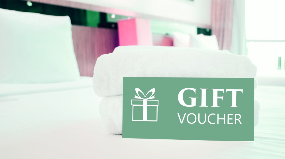 gift voucher card placed on bed | Ways To Improve Hotel Guest Experience | hotel guest | customer satisfaction