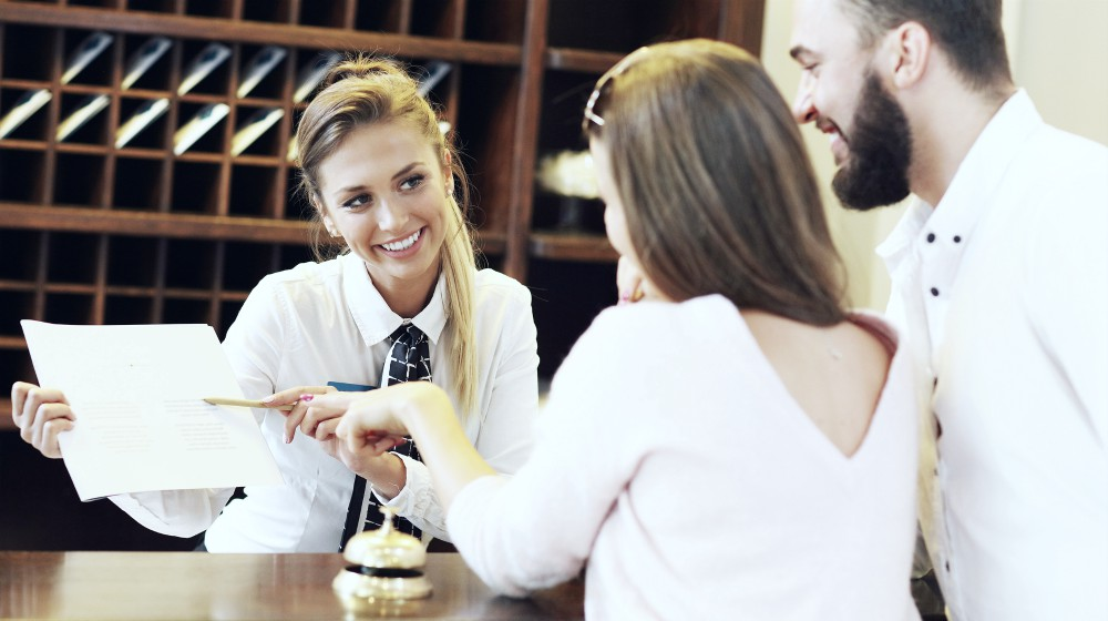 picture of couple and receptionist talking at the counter | Ways To Improve Hotel Guest Experience | hotel guest | customer satisfaction