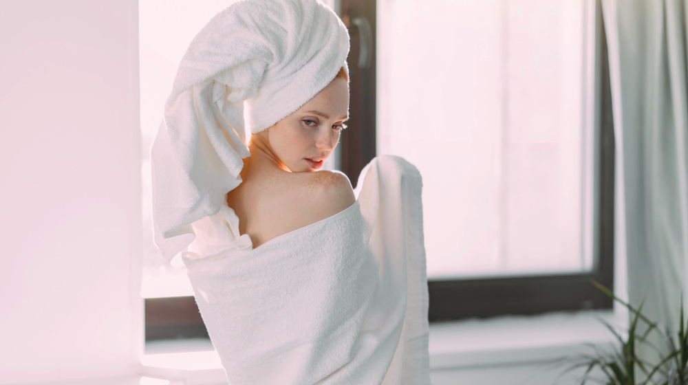 Rear shot of slim young female model wrapped in towel with turban on head | How To Choose The Best Luxury Bath Towels | luxury towels | luxury beach towels | Featured