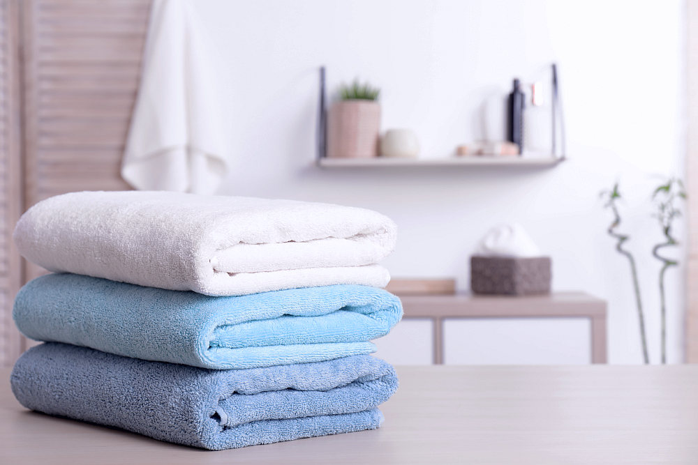 Stack of fresh towels on table in bathroom | How To Choose The Best Luxury Bath Towels | luxury towels | best luxury towels