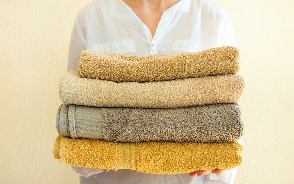 Young caucasian woman holds in hands stack of clean folded terry towels | How To Choose The Best Luxury Bath Towels | luxury towels | luxury towels