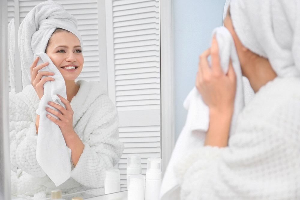 Young woman wiping her face with towel in bathroom | How To Choose The Best Luxury Bath Towels | luxury towels | luxury bath towels