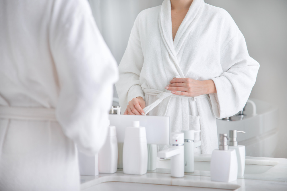 Close up of body of young woman tying up belt of white bathrobe in front of the mirror | Airbnb Bathroom Essentials To Stock For Your Guests | airbnb supplies