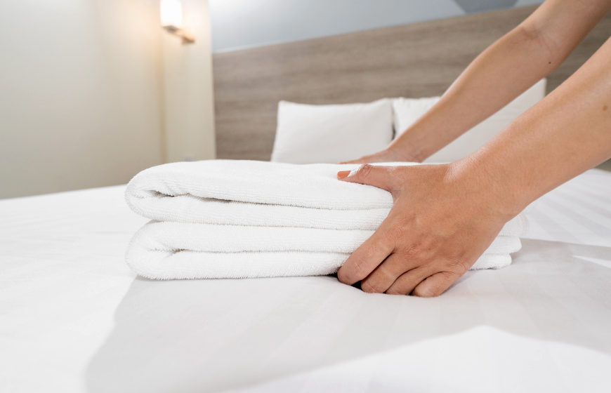 Close-up of hands putting stack of fresh white bath towels on the bed sheet | How Often Should You Replace Your Airbnb Linens And Towels | how often should you replace your towels | how often to replace towels | Featured