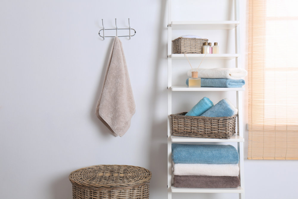 Shelving unit and rack with clean towels and toiletries near white wall | Airbnb Bathroom Essentials To Stock For Your Guests | airbnb amenities