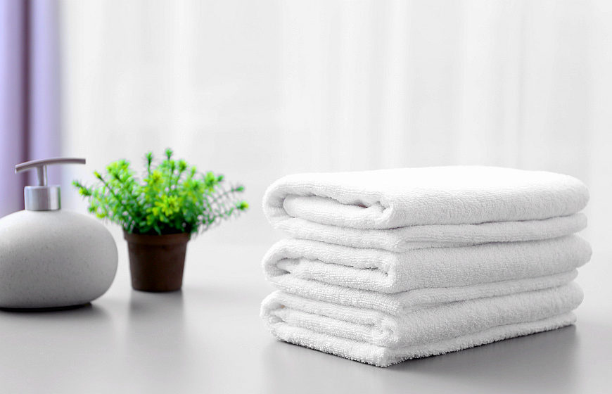 Stack of white clean towels on table in bathroom | Why A White Towel Should Be A Bathroom Staple | white bath towel | Featured